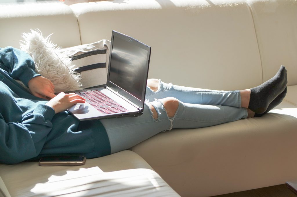 Girl sitting on the white couch and using her laptop content marketing trends