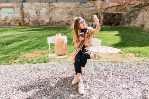 Attractive hipster girl wearing beige coat makes selfie for instagram profile during coffee break in