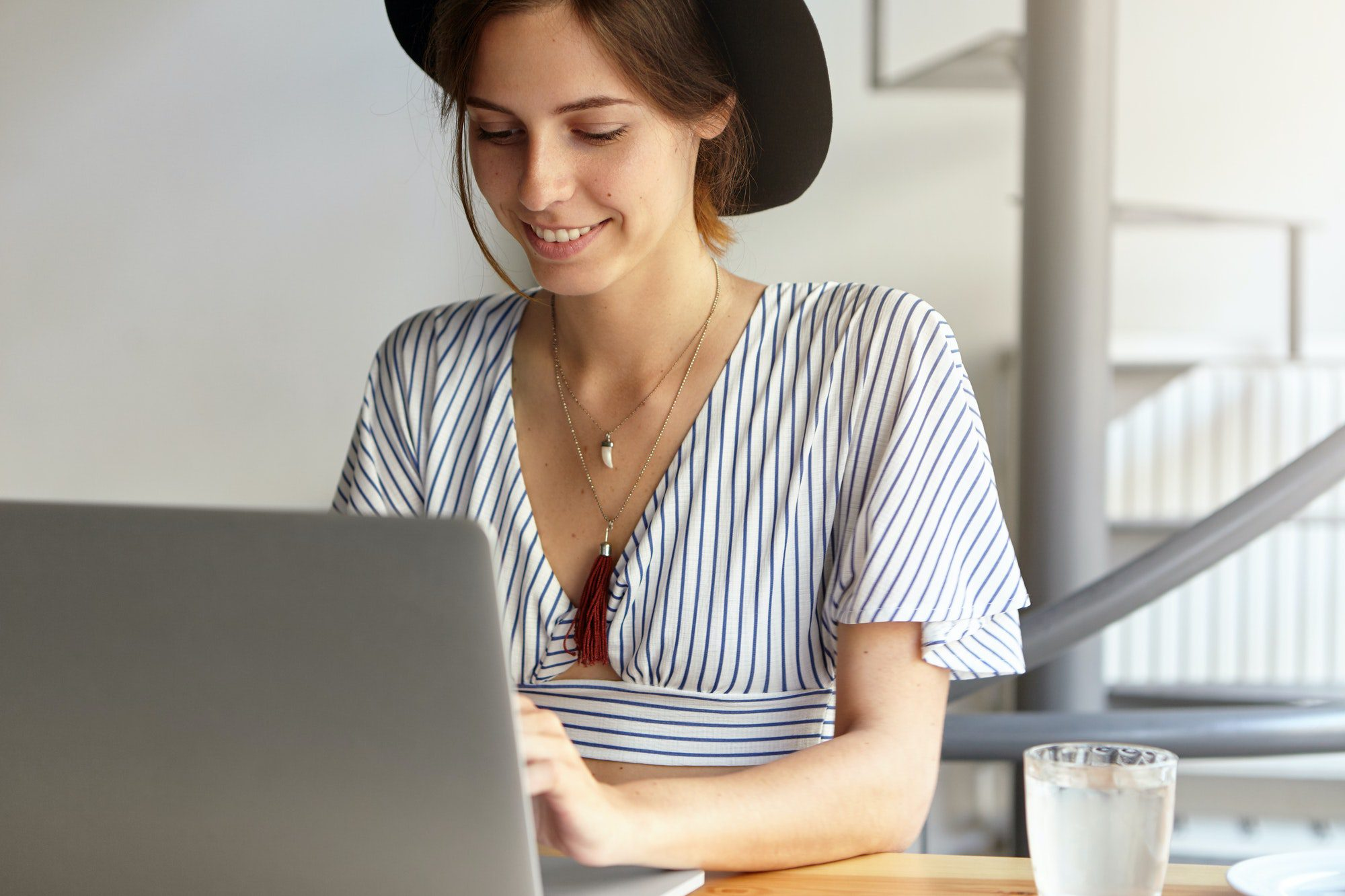 Beautiful woman blogger sitting in front of laptop computer while working remotely on content for ne