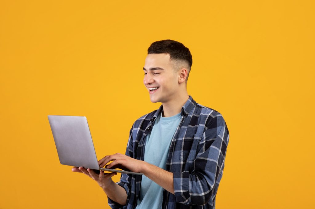 Happy young man looking at laptop screen with smile, watching interesting web content on orange