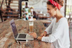 Sideways portrait of smiling female copywriter does remote work on laptop computer, enjoys tasty mil